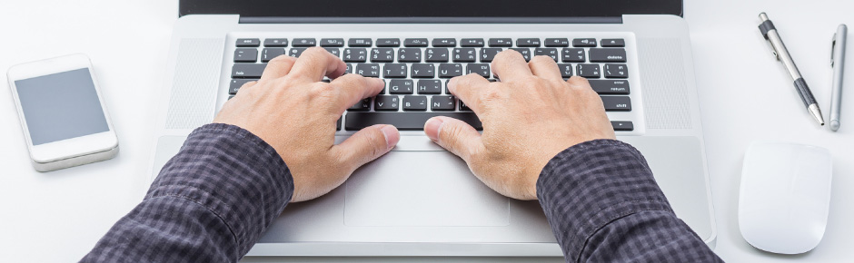 A man uses a laptop keyboard, with a smartphone and mouse beside him.